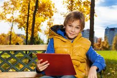 有纸的男孩在长凳 免版税库存图片
