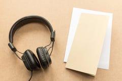 有纸笔记的耳机关于木书桌在音乐演播室 免版税库存照片