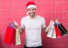 有纸袋的圣诞老人顾客在桃红色背景 免版税图库摄影