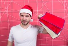 有纸袋的超级圣诞老人顾客在桃红色背景 免版税库存图片