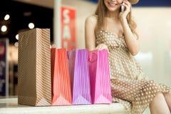 有纸袋的购物妇女谈话在电话 免版税库存图片