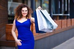 有纸购物袋的愉快的微笑的可爱的少妇 免版税库存照片
