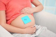 有纸贴纸的孕妇在肚子,特写镜头 图库摄影
