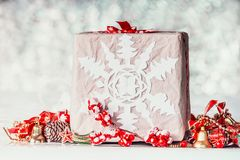 有纸雪花和红色装饰的手工制造圣诞节礼物盒在bokeh背景 免版税库存图片