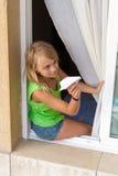 有纸飞机的小白种人女孩在窗口里 免版税图库摄影