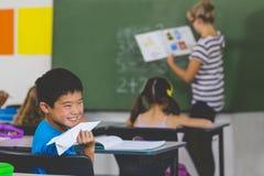 有纸飞机的男孩,当老师教学在教室时 免版税库存照片