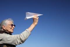 有纸飞机的高级妇女 库存图片