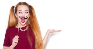 有纸髭的滑稽的十几岁的女孩在棍子 免版税库存图片