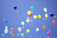 有纸鸽子的五颜六色的气球被栓对他们飞行在天空蔚蓝 免版税库存图片