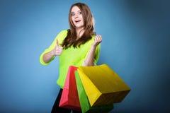 有纸购物袋的愉快的女孩。销售。 库存照片