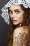 有纹身花刺、dreadlocks和鞋带披肩的美丽的女孩 库存照片