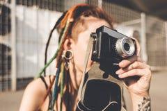 有纹身花刺和dreadlocks的少女拍在都市工业背景的照片 免版税图库摄影