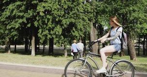 有纹身花刺的一个金发碧眼的女人在公园骑一辆时兴的自行车 股票视频