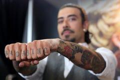有纹身花刺的人在手指 库存图片