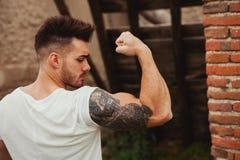有纹身花刺的坚强的人在外面他的胳膊 免版税库存图片