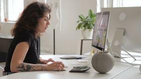 有纹身花刺的妇女与与计算机一起使用打电话的分散 股票视频
