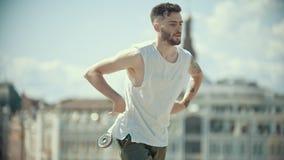 有纹身花刺的年轻时髦的有胡子的人在执行的白色衬衫锁在城市的背景的舞蹈元素 股票录像