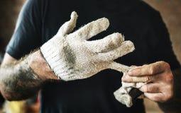 有纹身花刺的杂物工拔出手套的 库存图片