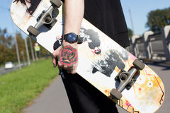 有纹身花刺的溜冰板者在他的胳膊 图库摄影