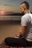 有纹身花刺的瑜伽人思考在莲花姿势的 免版税库存照片