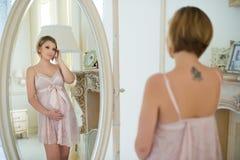 有纹身花刺的美丽的亭亭玉立的怀孕的女孩在看她自己的肩胛骨在镜子 免版税库存图片