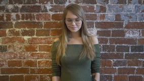 有纹身花刺的美丽的女孩看照相机并且微笑着,当站立对红砖墙壁时 股票录像