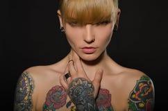 有纹身花刺的美丽的金发碧眼的女人在身体 免版税库存图片