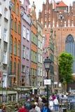 有经济公寓住宅和16世纪哥特式圣玛丽` s教会,格但斯克,波兰五颜六色的门面的Mariacka街道  图库摄影