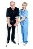 有经验的医师在恢复进程中的协助解决她的患者 免版税库存照片