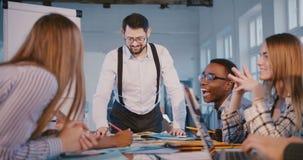 有经验的年轻上司商人与不同种族的伙伴一起工作在桌后的现代时髦办公室会议上 股票视频