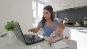 有结合育儿和研究手提电脑的哭泣的小孩男孩的多任务妈妈坐在桌上在厨房里 股票录像