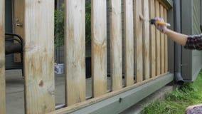 有绘木大阳台栏杆的油漆刷的妇女 o 股票视频