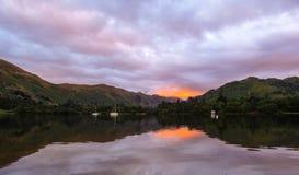 有给反射的小船的一个湖红色覆盖了日落 库存图片