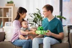 有给生日礼物的婴孩的母亲父亲 免版税库存照片