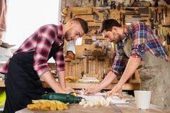 有统治者和图纸的木匠在车间 免版税库存图片