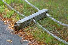 有绳索扶手栏杆的残破的岗位在地面上 免版税库存图片