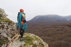 有绳索海湾的专业登山家在一个高岩石站立并且调查距离 库存图片