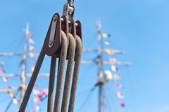 有绳索的与色的旗子的滑轮反对天空蔚蓝和帆柱 库存图片