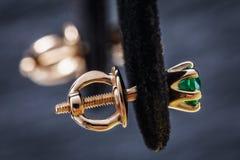 有绿宝石的金耳环在立场 免版税库存图片