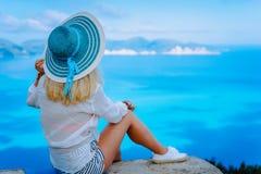有绿松石太阳帽子的可爱的女性游人享受惊人的天蓝色的海景,希腊的 在海的Cloudscape阴影 免版税库存图片