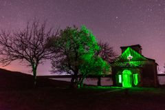 有绿灯里面和开花的树附近的nightscape的被放弃的教会 库存照片
