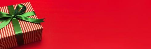 有绿色丝带的礼物盒在红色背景顶视图舱内甲板位置 假日概念、生日礼物、前新年或者圣诞节礼物盒 免版税库存图片
