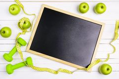 有绿色哑铃、苹果和测量的轻拍的空的黑板 免版税库存照片