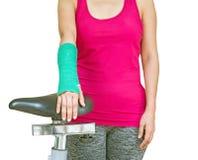 有绿色在手边被熔铸的和胳膊的伤害妇女佩带的运动服 免版税库存图片