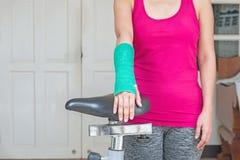 有绿色在手边被熔铸的和胳膊的伤害妇女佩带的运动服 免版税库存照片