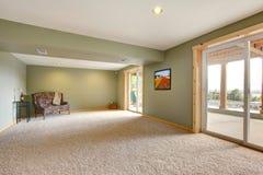 有绿色墙壁的底层大新的客厅。 免版税库存照片