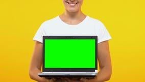 有绿色屏幕的快乐的妇女陈列膝上型计算机到照相机,网络购物里 股票录像
