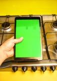 有绿色屏幕的片剂有厨房的背景 免版税库存照片