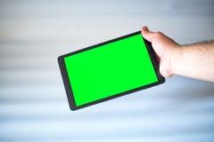 有绿色屏幕的片剂紧固单手在白色背景的 免版税库存照片