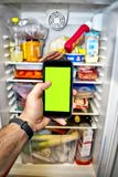 有绿色屏幕的电话有冰箱的底部的 免版税库存图片